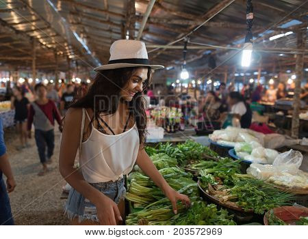 Young Woman Choosing Green Potherbs On Market Girl Shopping On Traditional Street Bazaar