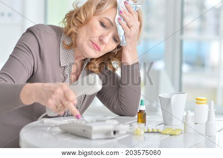 Portrait of a sick mature woman calling doctor