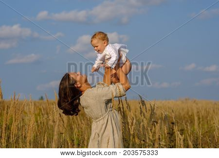 mother with a baby at the hands of European appearance in ethnic Russian costumes