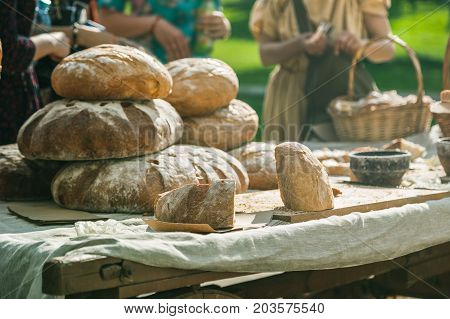 People Choosing Bread On The Table Of Bread Seller. Outdoors Summer Trading