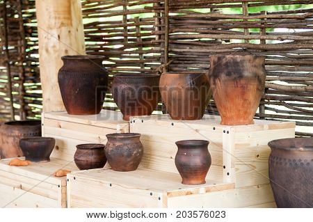 Different Ceramic Pots On A Wooden Table Near Wicker Wall, Selective Focus