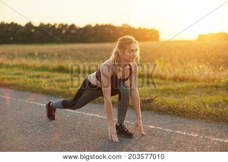 Attractive Female Wearing Sport Shoes And Clothes, Doing Sport Exercises On Road Against Sunset, Lik