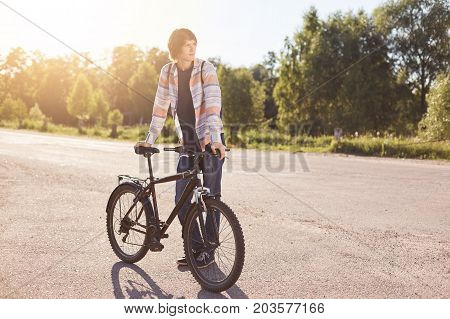 Pensive Teenage Boy Standing On Road, Keeping Hand On Handle Bar Of His Bike, Waiting For Others Cyc