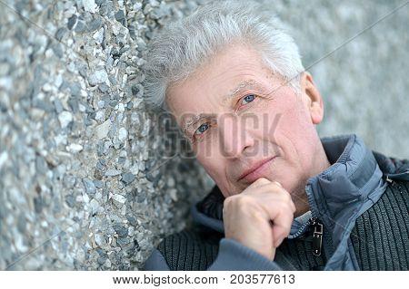 Close up portrait of senior man holding hand on chin