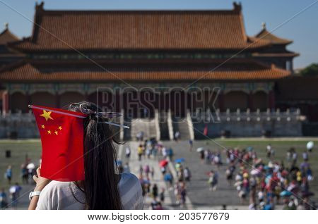 Beijing China - July 29 2012: Young Chinese girl with a Chinese Flag in her head at the Forbidden City in the city of Beijing in China