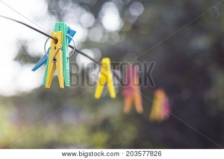 colored clothespins hanging on a rope with blurred background