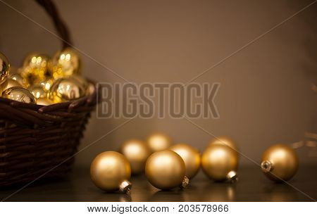 shiny and matt Christmas tree toys golden color in a wicker basket with a branch of the tree
