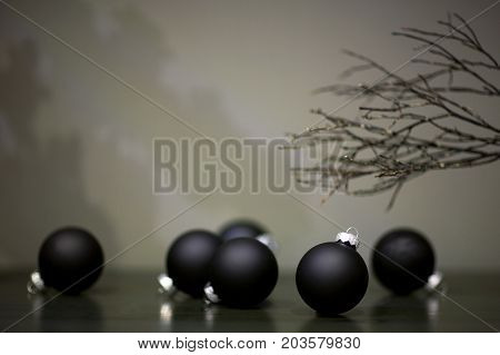 christmas tree toys matte black color and branch of a tree on a gray background