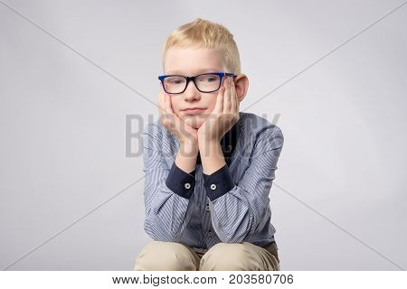 Portrait of caucasian blond boy in glasses looking with bored facial expression to camera on white background. He holds hands near face