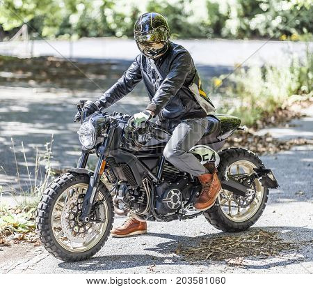 Cool looking motorcycle rider on custom made scrambler style cafe racer in the park