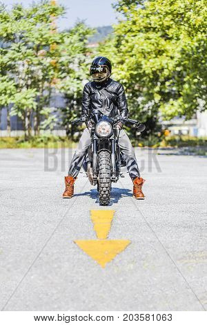 Cool looking motorcycle rider on custom made scrambler style cafe racer on the road with an arrow sign