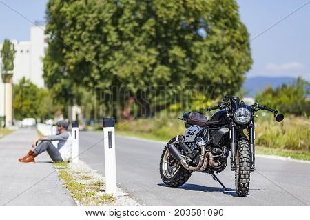 Cool looking motorcycle rider sitting near custom made scrambler style cafe racer