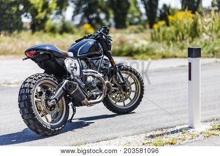 Cool looking custom made scrambler style cafe racer standing on road