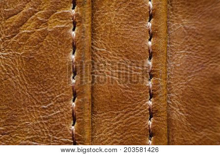 Texture of brown leather with stitches. Element of leather clothing close-up. Seams on leather products