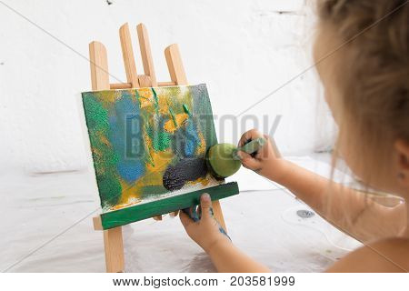 Creative little painter in art studio. Early childhood education, painting process, interesting hobby for children, artistic concept