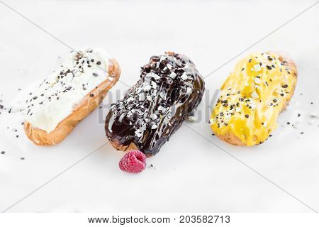 Three coloured Eclair with raspberries on white background