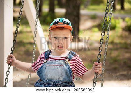 Happy little boy swinging on chain swing. Outdoor playground