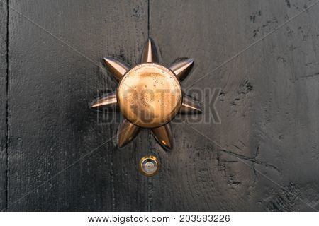 closeup of a copper doorknob with a small peephole under it