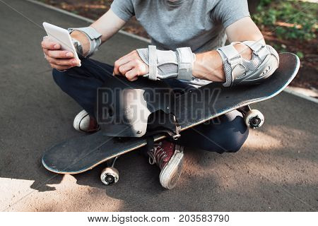 Professional skateboarder checking online network. Extreme sport challenge combining with active social life, internet and mobile phones in sportive urban lifestyle and culture of young people