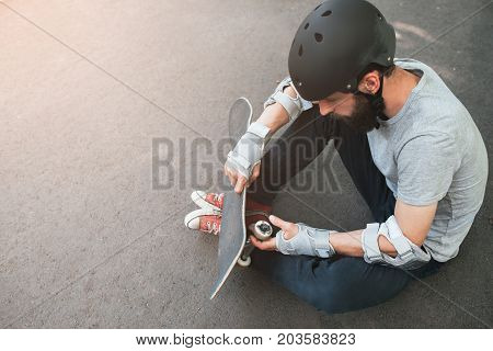 Professional skater checks his skateboard after training. First step in skateboarding sport challenge, failure and frustration, bad day for win. Skateboarder safety equipment backdrop with free space
