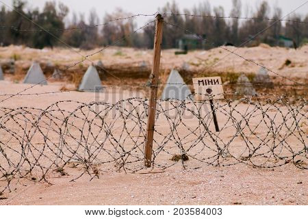 The sign Bomb on the coast. The mined part of the shore. Bomb translation from Ukrainian text. Fenced with barbed wire plot of land.
