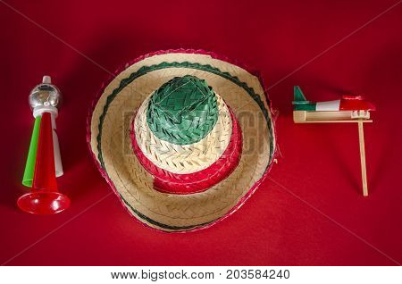 Trumpet, hat and noisemaker against red background. Accessories for mexican Independence Day celebration