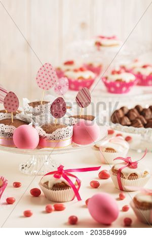 Easter cupcakes decorated with pink candy paper eggs and ribbons. Selective focus.