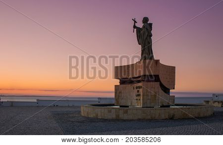 The statue of Saint Goncalo patron of mariners near Atlantic ocean. Sunrise picture with violet light from sun rising. Saint Goncalo with cross blessing to sailors during oversea discoveries.