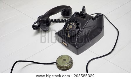 Telephone antique black color Speaker move out for show a button for hang on Isolate on white wood floor has copy space.