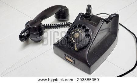 Telephone antique black color and speaker lift out to show option is button Isolate on white wood floor has copy space.