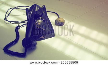 Antique telephone black color and speaker is on the telephone body Isolate on white wood floor has copy space.