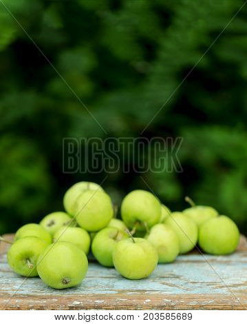 Homemade rustic green apples on an old stool. Selective focus.