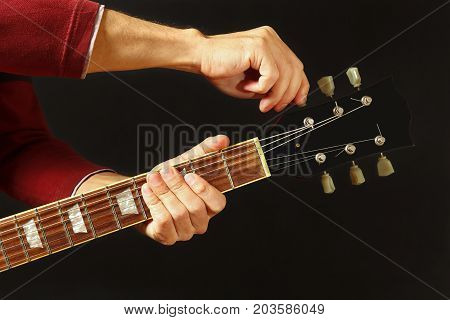Hands of musician tunes the guitar on a dark background