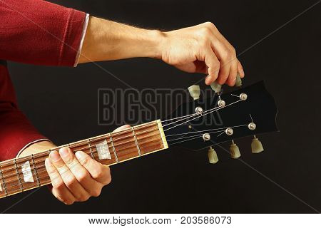 Hands of rock musician tunes the guitar on a dark background