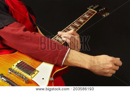 Hands of rock guitarist playing the guitar on a dark background