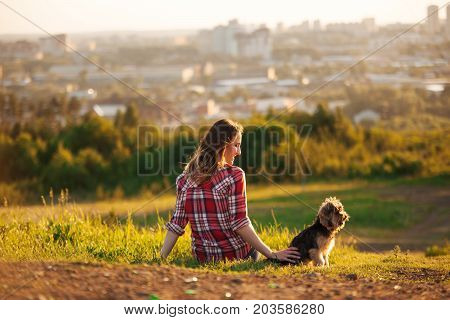 Young Woman Back In A Red Plaid Shirt With Her Pet Yorkshire Terrier Sitting On The Grass In A Park.