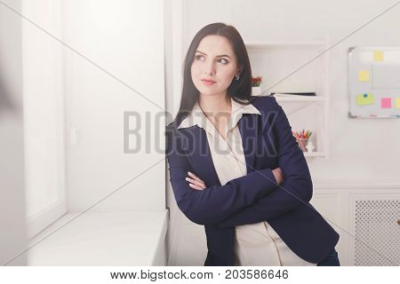 Creative thinking. Ambitious elegant business woman in formal wear standing at workplace and looking through window