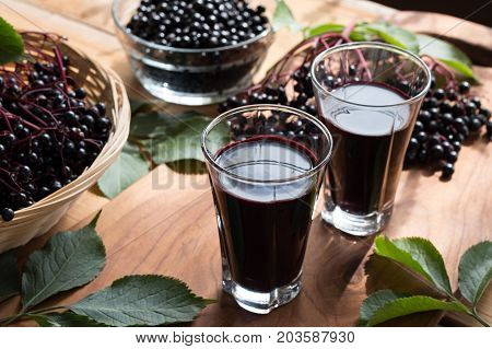 Two glasses of elderberry syrup with fresh elderberries in the background