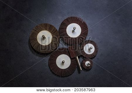 Flap Wheel. A pile of color abrasive Flap Wheel industrial on wood background texture. sandpaper for metal working