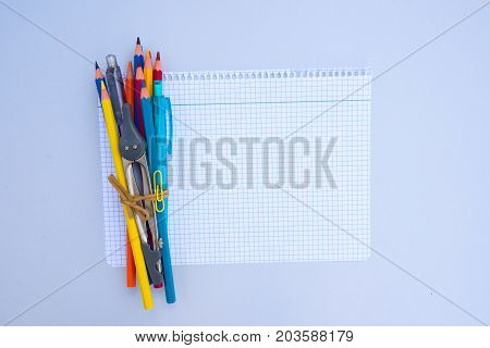 back to school concept - school supplies on ruled paper with copy space