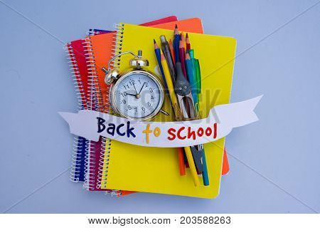 back to school concept - alarm clock and school supplies on blue with back to school letters on ribbon