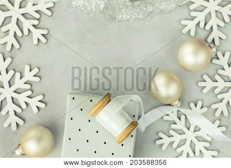 Gift boxes wrapped in silver paper. Wooden spool with white curled silk ribbon Christmas baubles snow flakes arranged in frame. Copy space for text. Clean scandinavian minimalist style.