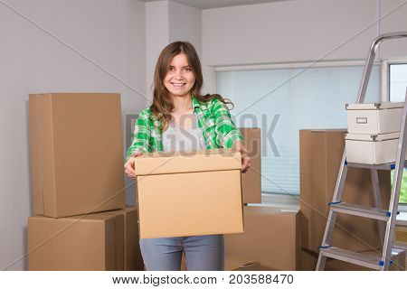 Portrait of woman carrying cardboard box in new house - Moving, new home and people concept.