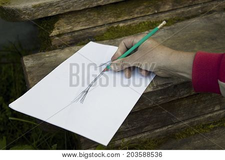 Man drafting abstract plan on the wooden steps of the house, outdoor particular focus photo