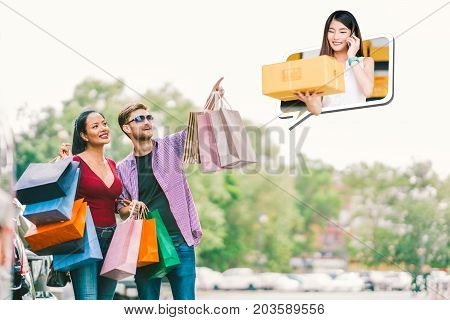 Happy Multi-ethnic couple with shopping bag white man point young small business owner lady sell goods on mobile phone call. E commerce shopaholic modern lifestyle or online shop marketing concept