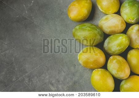 Bunch of scattered ripe juicy yellow and green plums arranged in border on dark stone background. Autumn fall harvest Thanksgiving. Poster template copy space for text. Vintage toning.