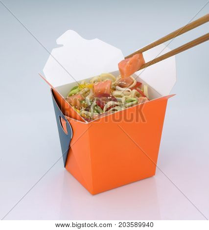 chinese food to takeaway. noodles with meat and vegetables in a cardboard box on a light background. takes chinese food with chopsticks