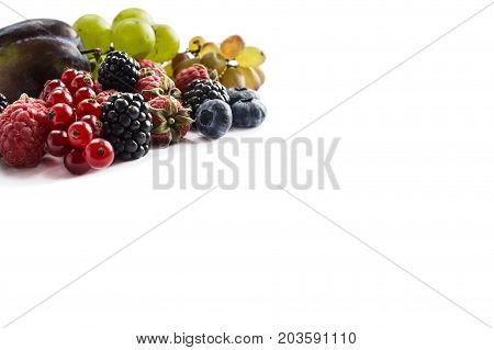 Various fresh summer berries on white background. Ripe raspberries red currants grapes blackberries blueberries and plums. Berries with copy space for text. Background berries.