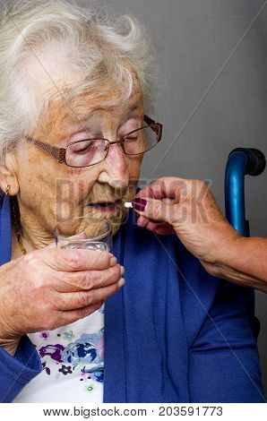 Senior Citizen taking Pill  A senior citizen, in a wheelchair, being given her medication by a carer.