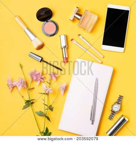 Modern woman accessories. Beauty products, smartphone, note book, accessories on a pastel background. Feminine composition